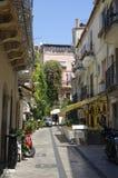 As bicicletas motorizadas estacionaram em uma da rua secundária da época alta famosa da cidade de Taormina em agosto de 2017er foto de stock