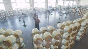 As bobinas brancas da fibra de vidro desenrolam linhas na oficina com grandes janelas filme