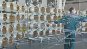 As bobinas da fibra de vidro desenrolam linhas processo movem-se e das monitores dos trabalhadores vídeos de arquivo