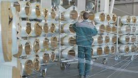 As bobinas próximas da fibra de vidro desenrolam trabalhadores no processo uniforme do controle filme