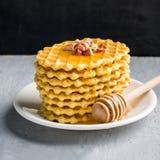 As bolachas, biscoitos modelados chuviscaram com mel com framboesa e amendoim em uma parede cinzenta do preto do fundo Imagem de Stock