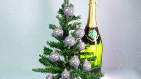 As bolas de ano novo em uma árvore do ano novo e em uma garrafa enorme do vinho espumante filme