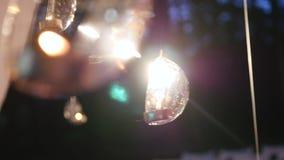 As bolas de vidro com velas penduram antes da janela video estoque