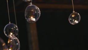 As bolas de vidro com velas penduram antes da janela vídeos de arquivo