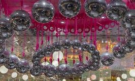 As bolas do disco penduram em cordas cor-de-rosa Fundo com muitas bolas do disco fotos de stock