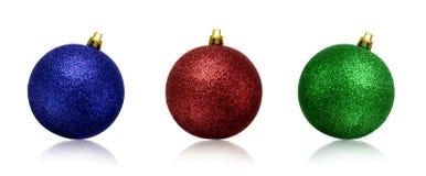 As bolas do Natal ou as quinquilharias verdes, azuis e vermelhas isolaram o fundo branco fotos de stock