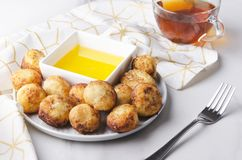 As bolas fritadas deliciosas do queijo serviram com mel e copo do chá preto Ajuste do café da manhã saboroso imagem de stock