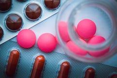 As bolhas com tabuletas coloridas e os comprimidos cor-de-rosa são derramadas de um frasco de vidro em um fundo azul branco A vis fotografia de stock royalty free