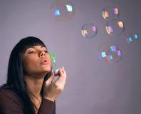 As bolhas da menina e de sabão Fotografia de Stock Royalty Free