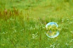 As bolhas de sabão em um campo verde voam a favor do vento O conceito da luminosidade e do airiness Fotografia de Stock