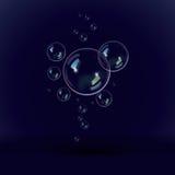 Bolhas de sabão em um fundo azul preto Imagens de Stock Royalty Free