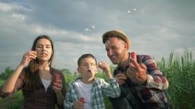 As bolhas de sab?o de sopro da fam?lia e o riso no movimento lento, no rapaz pequeno com mum e no paizinho em camisas de manta t? vídeos de arquivo
