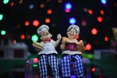 As bonecas da família sentam-se com sorriso junto caixa de presente colorida pelo Natal e o ano novo feliz no fundo colorido Foto de Stock
