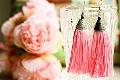 As borlas dos brincos das senhoras fecham-se acima da vista com fundo colorido bonito Conceito da forma de Famales dos acessórios fotografia de stock