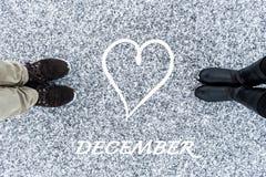 As botas masculinas e fêmeas que estão no símbolo do coração com texto dezembro no asfalto cobriram a superfície corajoso da neve Fotos de Stock Royalty Free