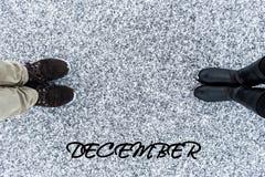 As botas masculinas e fêmeas que estão no símbolo do coração com texto dezembro no asfalto cobriram a superfície corajoso da neve Fotografia de Stock