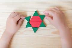 As brincadeiras com blocos coloridos, criam um asterisco em um fundo de madeira claro Fotos de Stock