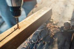 As brocas do trabalhador um furo na barra com uma chave de fenda conectam a fatura da mobília fotografia de stock royalty free
