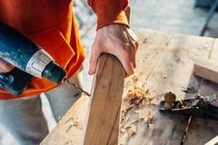 As brocas do trabalhador um furo na barra com uma chave de fenda conectam a fatura da mobília foto de stock royalty free