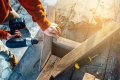 As brocas do trabalhador um furo na barra com uma chave de fenda conectam a fatura da mobília fotos de stock