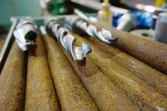 As brocas encontram-se em uma cremalheira perto da máquina e estão-se prontas para furar um furo fotografia de stock