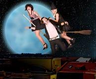 As bruxas em vassouras carregam o homem de encontro ao céu da estrela da lua Imagens de Stock Royalty Free