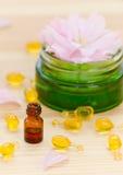 As cápsulas do cosmetik natural para a cara, uma garrafa pequena do ouro com óleo essencial e aumentaram no de madeira foto de stock