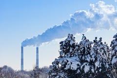 As câmaras de ar industriais fumam na frente dos abetos vermelhos do céu azul e do inverno Imagens de Stock Royalty Free