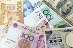 As cédulas da moeda espalharam através do quadro que inclui moedas principais do mundo imagem de stock