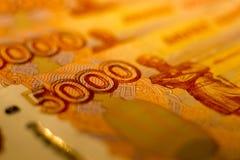 As cédulas do dinheiro do russo com valor o mais grande 5000 rublos fecham-se acima Tiro macro de cédulas alaranjadas Foto de Stock