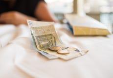 As cédulas e as moedas do Euro encontram-se em um pagamento branco da toalha de mesa a entrega de um almoço do café da manhã Imagem de Stock Royalty Free