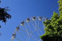 As cabines brancas da roda de Ferris no fundo do céu azul imagens de stock