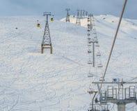 As cabines da gôndola, Ski Lift e o esqui da montanha inclinam-se durante o wint Imagem de Stock