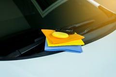 As cabras-montesas dos limpadores muitos colorem o pano e a cera amarela da esponja com carro branco Imagens de Stock