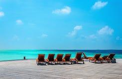 As cadeiras de plataforma alaranjadas de madeira em um cais no fundo dos azuis celestes molham, Oceano Índico, Maldivas Fotos de Stock