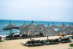 As cadeiras de praia na areia branca encalham com o céu azul e o sol nebulosos Fotografia de Stock