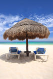 As cadeiras de praia sob o palapa cobriram com sapê a cabana Fotos de Stock Royalty Free