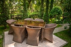As cadeiras de vime e a tabela est?o no jardim perto das ?rvores imagem de stock