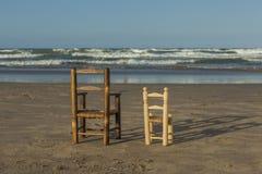 As cadeiras de vime pequenas de vista traseira levantam-se no litoral Fotos de Stock Royalty Free