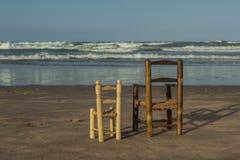 As cadeiras de vime pequenas de vista traseira levantam-se no litoral Imagem de Stock