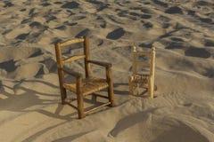 As cadeiras de vime pequenas levantam-se na praia da areia Imagem de Stock Royalty Free