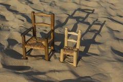 As cadeiras de vime pequenas levantam-se na praia da areia Foto de Stock