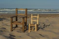 As cadeiras de vime pequenas levantam-se no litoral Imagem de Stock Royalty Free