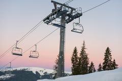 As cadeiras do elevador de esqui no inverno recorrem contra um céu bonito no por do sol foto de stock royalty free