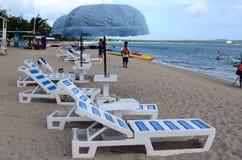As cadeiras e o guarda-chuva de praia no oceano branco da areia encalham Foto de Stock Royalty Free