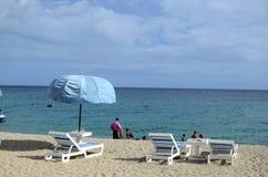 As cadeiras e o guarda-chuva de praia no oceano branco da areia encalham Fotos de Stock