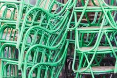 As cadeiras pintadas verde do metal com de madeira sentam t seguinte exterior empilhado imagens de stock