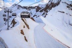 As cadeiras vagas do elevador do cabo aéreo de uma estância de esqui vazia em um cirque nevado da montanha inclinam-se no fundo e Fotos de Stock Royalty Free