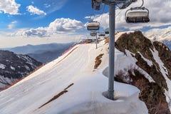 As cadeiras vagas do elevador do cabo aéreo de uma estância de esqui vazia em um cirque nevado da montanha inclinam-se no fundo e Imagens de Stock