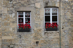 As caixas de janela enchidas com as flores vermelhas decoram a fachada de uma casa (França) Imagens de Stock